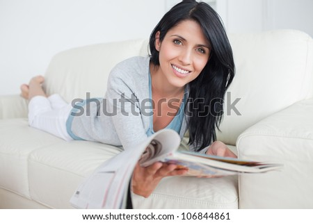 Woman holding a magazine while laying on a couch in a living room - stock photo