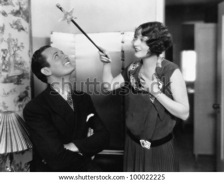 Woman holding a magic wand over her friends head - stock photo