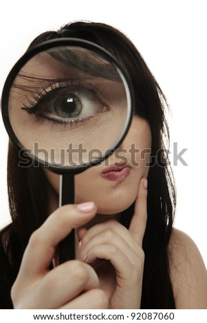 woman holding a magnifying glass up to her eye so it looks really big - stock photo