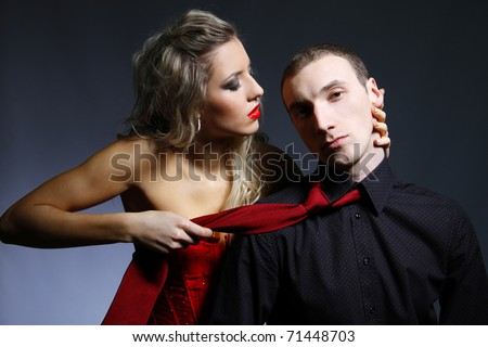 woman holding a man for a tie - stock photo