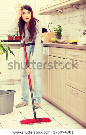 Woman holding a mop and cleaning kitchen floor  - stock photo