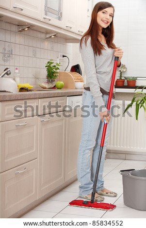 woman holding mop cleaning kitchen floor stock photo 174525872