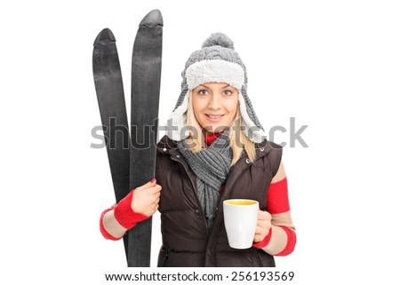 Woman holding a pair of skis and drinking hot tea isolated on white background - stock photo