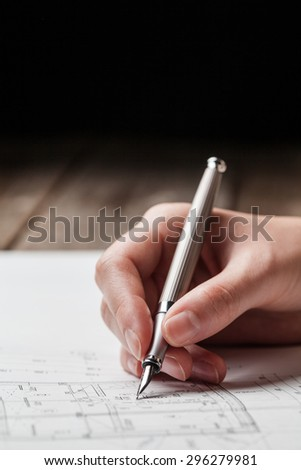 woman holding a pen over a house blueprint