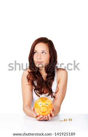 Woman holding a piggy bank and daydreaming of all the things she can do or buy with the money she has saved - stock photo