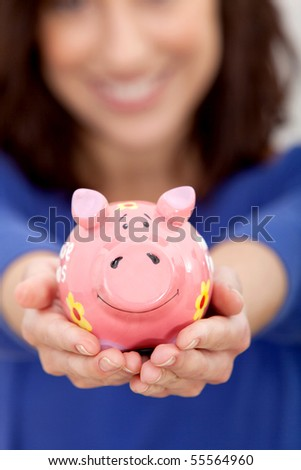 Woman holding a piggy bank in her hands and smiling - stock photo