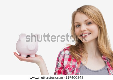 Woman holding a piggy bank on her hand against a white background