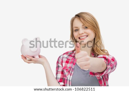 Woman holding a piggy bank with her thumb up against a white background - stock photo