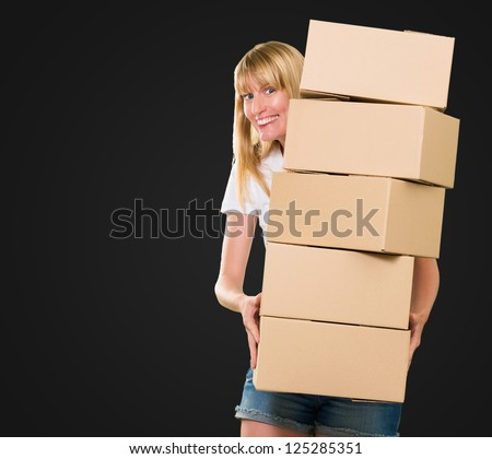 woman holding a pile of boxes against a black background - stock photo