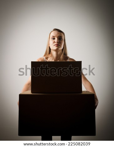 Woman holding a pile of packaged parcels. Woman doing something. - stock photo