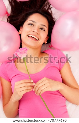 Woman holding a pink rose with ballons around her