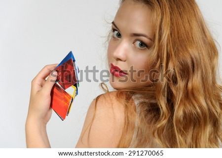 Woman holding a plastic card and thoughtfully looking up against a light background - stock photo