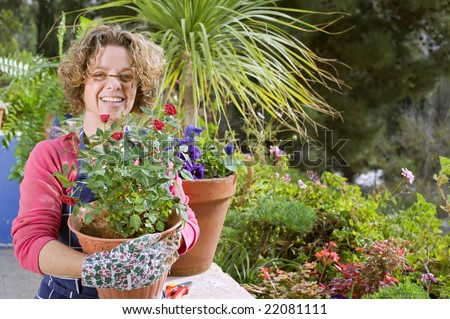 woman holding a pot of roses her garden - stock photo