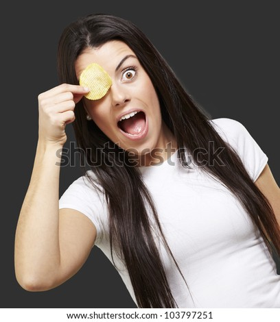 woman holding a potatoe chip in front of her eye against a black background - stock photo