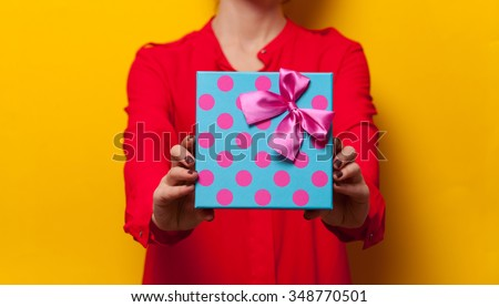 Woman holding a present box on yellow background - stock photo