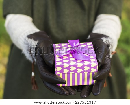 Woman holding a purple yellow gift box in autumn background - stock photo