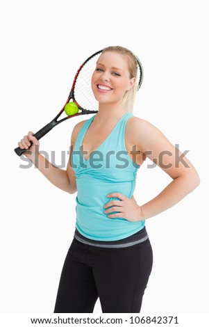 Woman holding a racquet behind her head against white background - stock photo