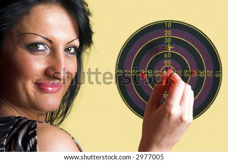 Woman holding a red dart over a center of a target - stock photo
