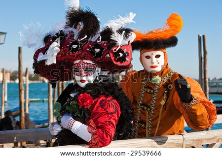 Woman holding a red rose in a black costume with a man in an orange costume at the Venice Carnival - stock photo
