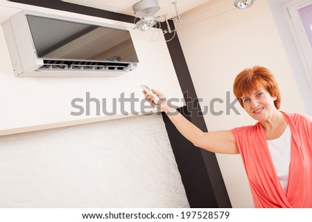 Woman holding a remote control air conditioner at home. Happy mature woman on sofa - stock photo