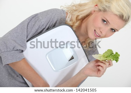 Woman holding a scale and a lettuce leaf - stock photo