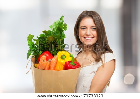 Woman holding a shopping bag full of fresh food - stock photo