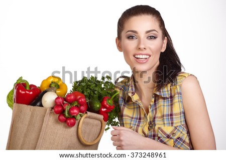 Woman holding a shopping bag full of fresh food, Isolated studio shoot