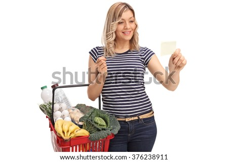 Woman holding a shopping basket and reading a piece of paper isolated on white background - stock photo
