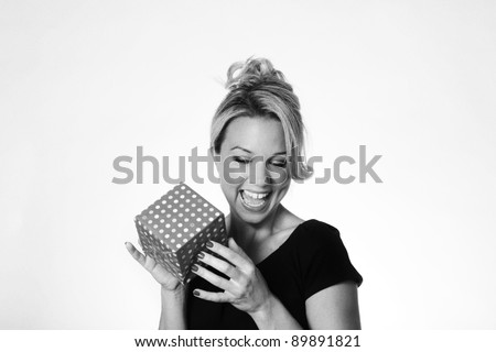 woman holding a small present think what could be inside - stock photo