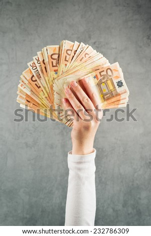 Woman holding a stack of fifty euro banknotes, selective focus and shallow depth of field - stock photo