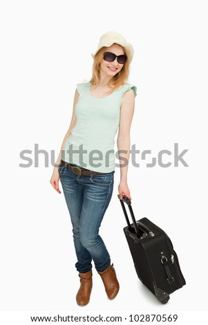 Woman holding a suitcase while standing against white background - stock photo