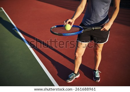 woman holding a tennis ball and racquet - stock photo