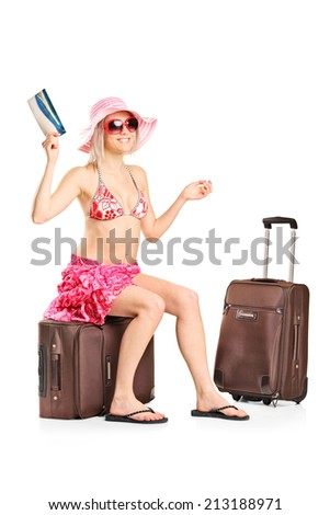 Woman holding a ticket seated on her baggage isolated on white background - stock photo