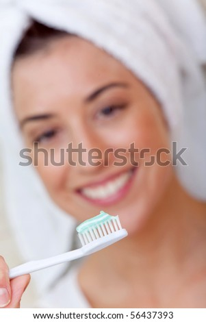 Woman holding a toothbrush in front of her face - stock photo