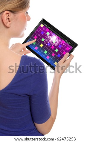 woman holding a touchpad pc, one finger touches the screen playing a retro arcade game - stock photo