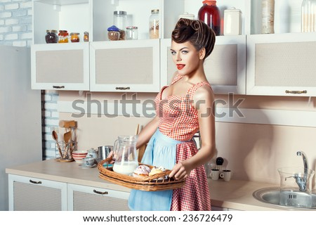 Woman holding a tray with dessert, she in the kitchen wearing an apron. - stock photo