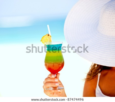 Woman holding a tropical cocktail at a beach resort - stock photo