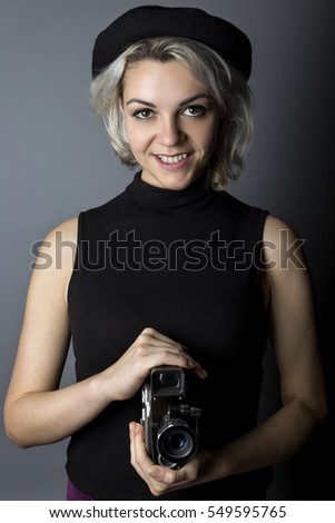 Woman holding a vintage video camera posing as a director, filmmaker, or cinematographer in the hollywood movie industry.  The image depicts creative arts.