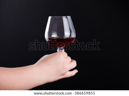 Woman holding a wine glass on black background