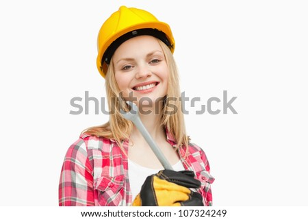 Woman holding a wrench while smiling against white background - stock photo