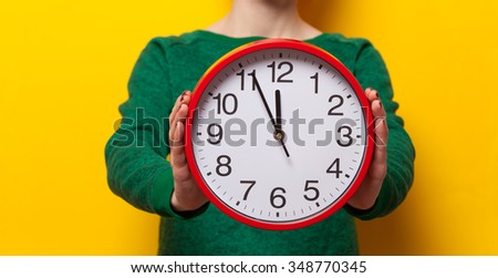 Woman holding alarm clock on yellow background - stock photo