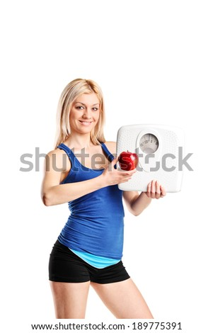 Woman holding an apple and a weight scale isolated on white background - stock photo