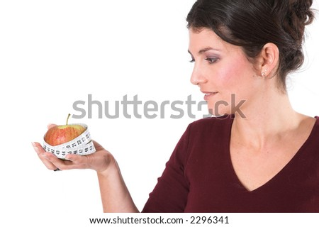 Woman holding an apple in her hand with a measuring tape around it - stock photo