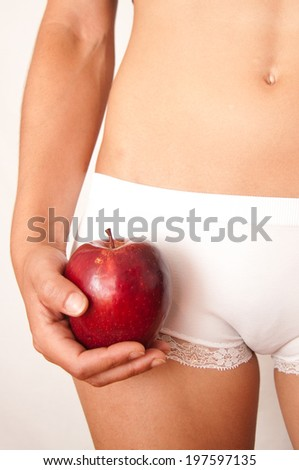 Woman holding an apple near her belly with hands