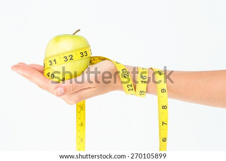 Woman holding an apple with tape measure on white background - stock photo