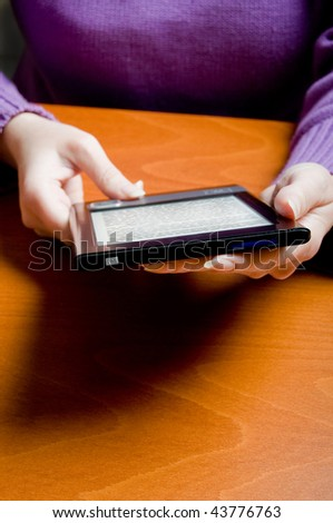 woman holding an electronic book reader - stock photo