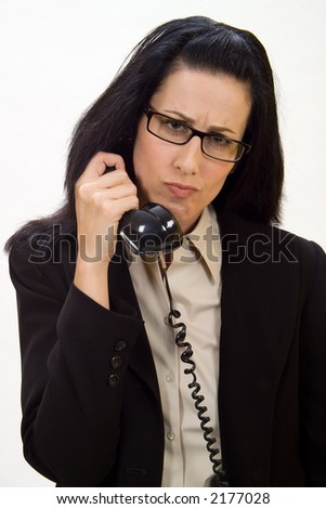 Woman holding an old school phone looking disturbed