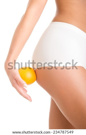 Woman holding an orange against her thighs, isolated in white - stock photo