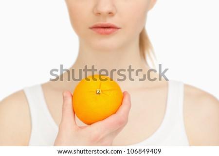 Woman holding an orange against white background - stock photo