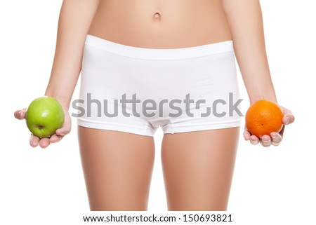 Woman holding an orange and apple without signs of cellulitis - stock photo